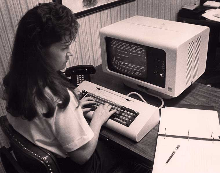 Black and white photo of woman at computer